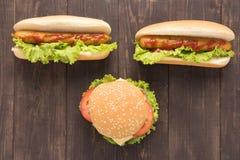Perritos calientes y hamburguesas en el fondo de madera Fotografía de archivo