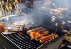 Perritos calientes y hamburguesas en la parrilla Imágenes de archivo libres de regalías