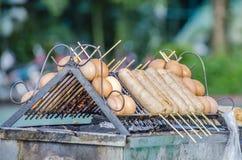 Perritos calientes y huevos en parrilla de la barbacoa Fotos de archivo