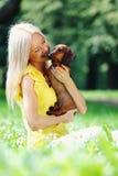 Perro basset de la mujer en sus brazos Foto de archivo
