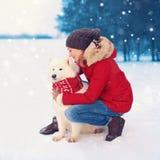 Perro blanco del samoyedo de la mujer del abarcamiento feliz del dueño en la Navidad del invierno Foto de archivo