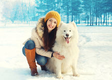 Perro blanco sonriente feliz del samoyedo del abarcamiento del dueño de la mujer en invierno Imagen de archivo libre de regalías
