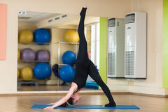 Perro boca abajo practicante de la yoga de la mujer Fotografía de archivo