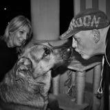 perro con sus amigos, él besa a uno de ellos mientras que está sonriendo el otro ¡un perro cariñoso! fotografía blanco y negro fotografía de archivo libre de regalías