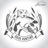 Perro de caza del logotipo de la caza con un pato salvaje en sus dientes y desig ilustración del vector