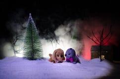 Perro de juguete - un símbolo del Año Nuevo debajo de la nieve contra la perspectiva del abeto ramifica El perro de juguete como  Imagen de archivo