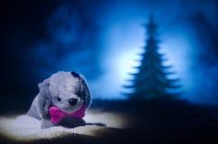 Perro de juguete - un símbolo del Año Nuevo debajo de la nieve contra la perspectiva del abeto ramifica El perro de juguete como  Imagen de archivo libre de regalías