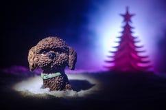 Perro de juguete - un símbolo del Año Nuevo debajo de la nieve contra la perspectiva del abeto ramifica El perro de juguete como  Fotos de archivo libres de regalías