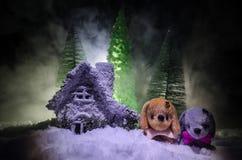 Perro de juguete - un símbolo del Año Nuevo debajo de la nieve contra la perspectiva del abeto ramifica El perro de juguete como  Fotografía de archivo libre de regalías