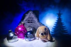 Perro de juguete - un símbolo del Año Nuevo debajo de la nieve contra la perspectiva del abeto ramifica El perro de juguete como  Imágenes de archivo libres de regalías