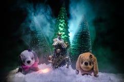 Perro de juguete - un símbolo del Año Nuevo debajo de la nieve contra la perspectiva del abeto ramifica El perro de juguete como  Foto de archivo libre de regalías