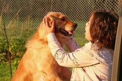Perro de la caricia de la muchacha Imagen de archivo libre de regalías