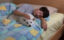 Perro de la familia que es acariciado por la muchacha adolescente en cama Imagen de archivo
