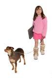 Perro de la toma de la muchacha para una caminata que lleva su computadora portátil Foto de archivo