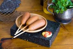 Perro de maíz en una tabla, salsa de tomate, mostaza, aún hogar de la vida, salchicha, empanado, delicioso, deliciosa Imagenes de archivo