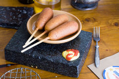 Perro de maíz en una tabla, salsa de tomate, mostaza, aún hogar de la vida, salchicha, empanado, delicioso, deliciosa Fotos de archivo