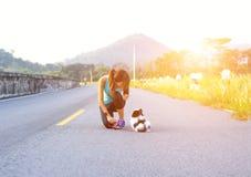 Perro de perrito y mujeres jovenes que corren ejercicio en el parque de la calle por la mañana Foto de archivo
