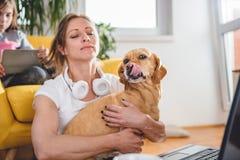 Perro del abarcamiento de la mujer que se sienta en piso Fotografía de archivo libre de regalías