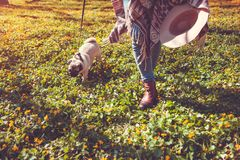 Perro del barro amasado de la mujer que camina en el perrito feliz del bosque de la primavera que corre entre las flores amarilla foto de archivo