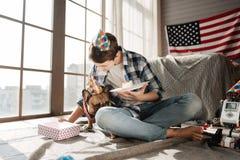 Perro del cumpleaños que oculta detrás de la pierna de su amo Fotos de archivo