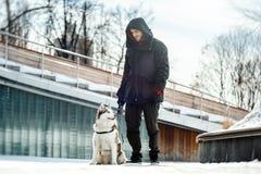 Perro del hombre y del husky siberiano en un paseo en parque moderno en día de invierno soleado imagenes de archivo