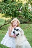 Perro grande divertido en gafas de sol y muchacha rubia linda en el vestido blanco al aire libre en parque Imagen de archivo libre de regalías