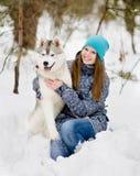 Perro hasky del abarcamiento adolescente de la muchacha en parque del invierno Fotografía de archivo