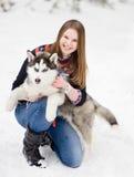 Perro hasky del abarcamiento del adolescente en nieve Imágenes de archivo libres de regalías