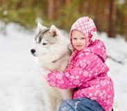 Perro hasky del abarcamiento del niño en parque del invierno Imagen de archivo libre de regalías