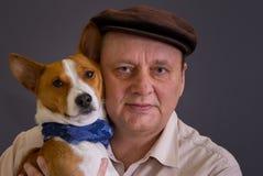 Perro joven del basenji que lleva el pañuelo azul y su el amo maduro que llevan el casquillo marrón Fotografía de archivo libre de regalías