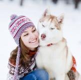 Perro lindo del abarcamiento adolescente de la muchacha en parque del invierno Fotografía de archivo libre de regalías