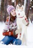 Perro lindo del abarcamiento adolescente de la muchacha en parque del invierno Imagen de archivo libre de regalías