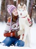 Perro lindo del abarcamiento adolescente de la muchacha en parque del invierno Foto de archivo libre de regalías