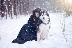 Perro lindo del abarcamiento de la muchacha del cuento de hadas en parque del invierno Foto de archivo