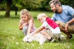 Perro que acaricia de los niños en verano Imagen de archivo libre de regalías