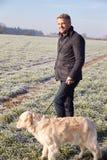 Perro que camina del hombre maduro en Frosty Landscape Foto de archivo