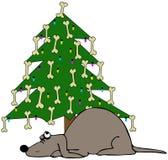 Perro que duerme bajo un árbol de navidad Fotografía de archivo