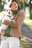 Perro que recorre de la mujer al aire libre en parque del otoño Fotos de archivo libres de regalías