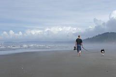 Perro que recorre del hombre en la playa Fotografía de archivo libre de regalías