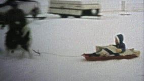 1973: Perro que tira violentamente del niño en el trineo de la nieve del invierno almacen de video