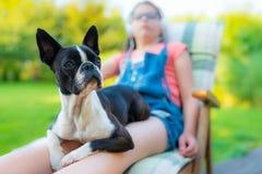Perro y adolescente que descansan en el jardín Imágenes de archivo libres de regalías