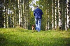Perro y dueño en el bosque Imagen de archivo libre de regalías