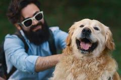Perro y su dueño - perro fresco y hombre joven que se divierten fotografía de archivo libre de regalías