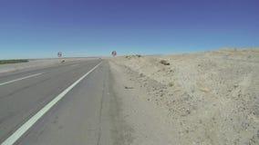 Perros en un camino en el desierto de Atacama/el paseo de la bicicleta almacen de metraje de vídeo