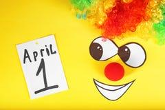 Perruque d'arc-en-ciel, nez de clown et note avec l'expression Image stock
