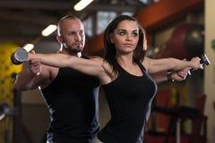 Persönliche Trainer-Showing Young Woman-Übung für Schultern Lizenzfreie Stockbilder