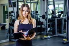 Persönliche Trainerfrau, die Klemmbrett mit Trainingsplan in der Turnhalle hält stockbilder