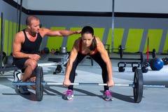 Persönlicher Kursleitermann der Turnhalle mit Gewichtsanhebenstangenfrau Lizenzfreies Stockbild