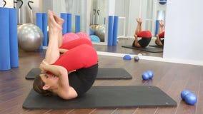 Persönlicher Trainer Aerobic pilates Frauen mit Schüler in Folge an der Turnhalle