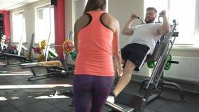 Persönlicher Trainer, den hübsches Mädchen die Übung für die Beinmuskeln auf dem Simulator überwacht, führt einen Mann mit einem  stock footage
